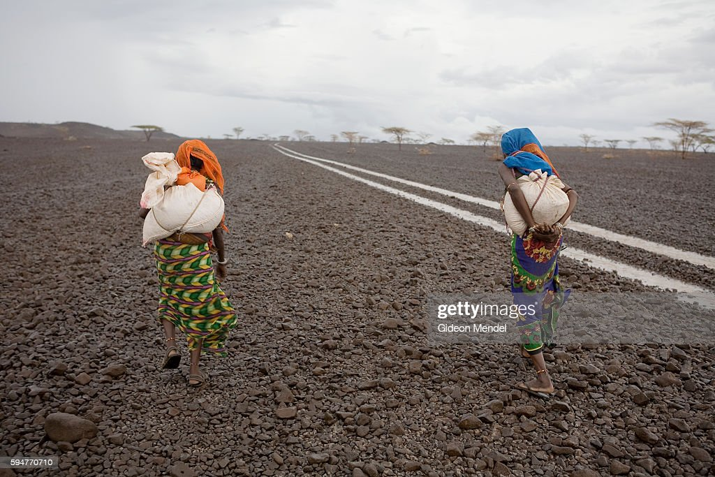 Gabra pastoralists Habima Muhamed and Adho Barille carry their monthly supplies of food aid as they walk back to their encampment through the rocky...