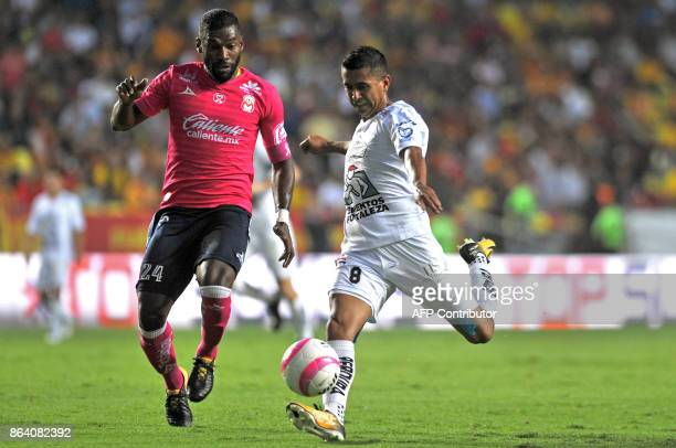Gabriel Achilier of Morelia vies for the ball with Elias Hernandez of Leon during their Mexican Apertura tournament football match at the Morelos...