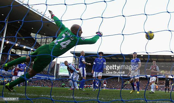 Gabriel Agbonlahor of Aston Villa scores the second goal past Everton keeper Tim Howard during the Barclays Premier League match between Everton and...