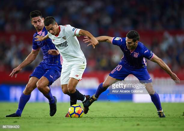 Gabriel Appelt of CD Leganes and Joseba Zaldua of CD Leganes competes for the ball with Wissam Ben Yedder of Sevilla FC during the La Liga match...