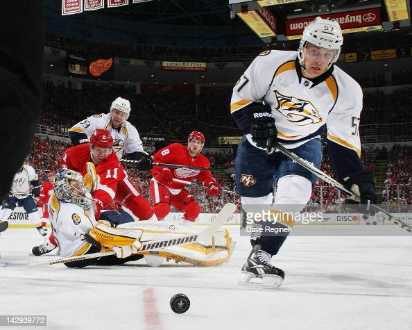 Gabriel Bourque of the Nashville Predators skates to the the puck while teammate Pekka Rinne tends net and Nick Spaling defends Dan Cleary of the...