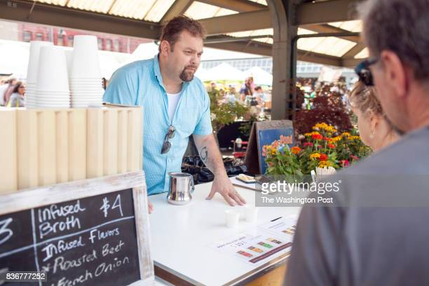 Gabriel Claycamp speaks passionately about his bone broth with customers at his cart during the Bellingham Farmers Market on Saturday 8/12/17