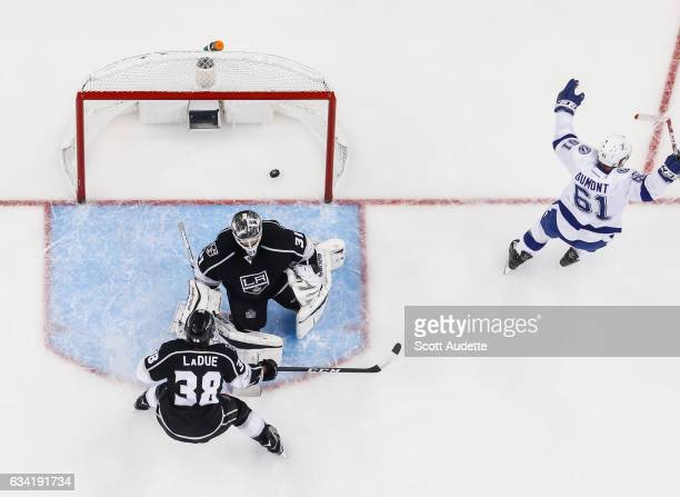 Gabriel Dumont of the Tampa Bay Lightning shoots the puck for a goal against goalie Peter Budaj and Paul LaDue of the Los Angeles Kings during the...