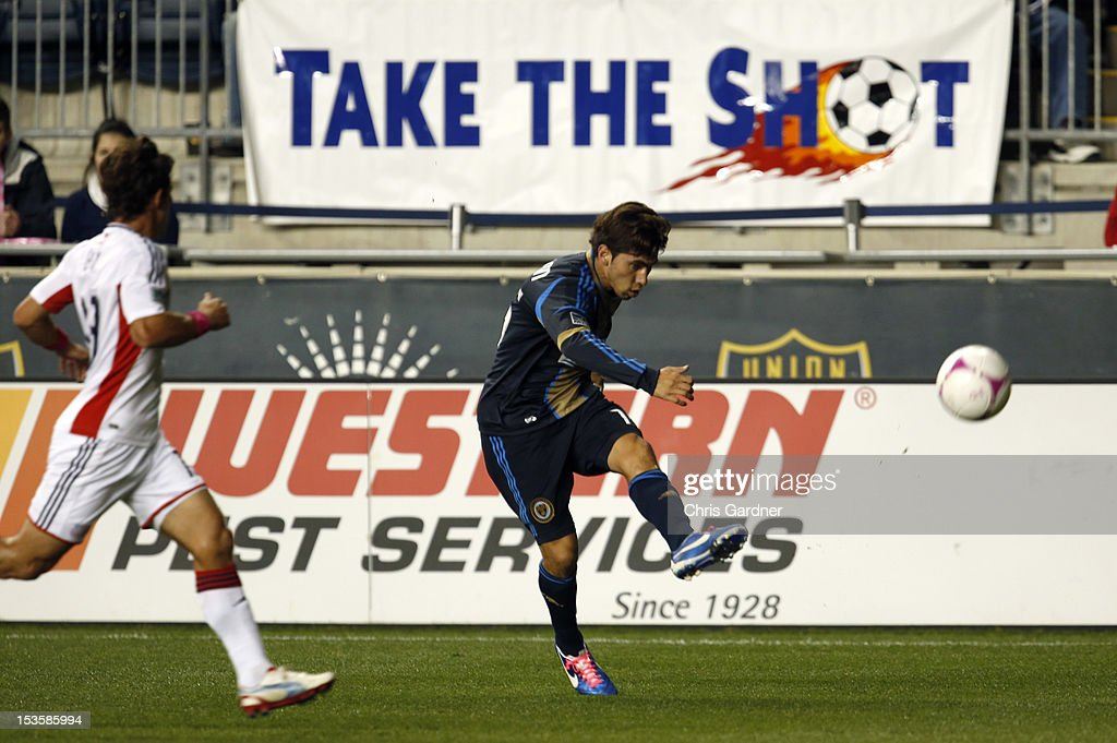 Gabriel Farfan #15 of the Philadelphia Union crosses the ball as he is covered by Ryan Guy #13 of the New England Revolution at PPL Park on October 6, 2012 in Chester, Pennsylvania.