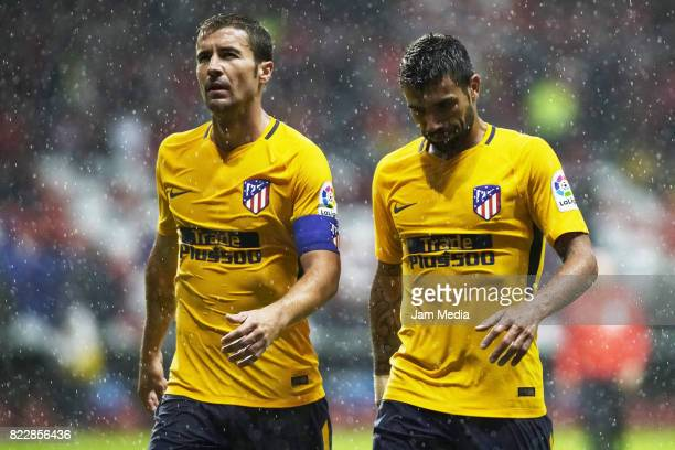 Gabriel Fernandez and Augusto Matias of Atletico de Madrid leave the field during a friendly match between Toluca and Atletico de Madrid as part of...