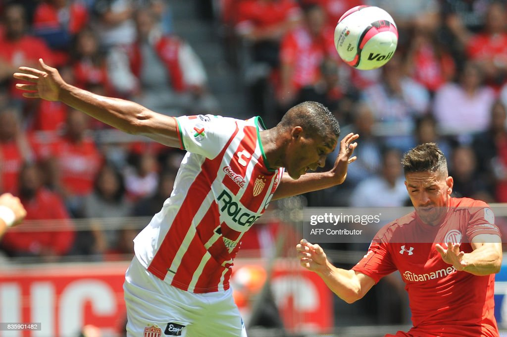Gabriel Hauche (R) of Toluca jumps for the ball with Bryan Beckeles of Necaxa during their Mexican Apertura football tournament match at the Nemesio Diez stadium in Toluca, Mexico, on August 20, 2017. /