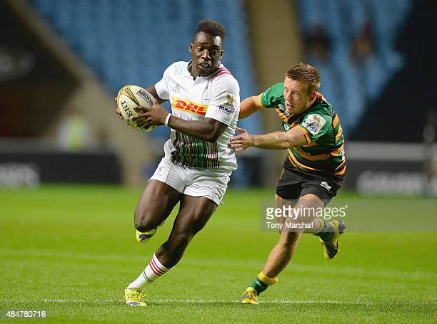 Gabriel Ibitoye of Harlequins escapes a tackle from Sam Olver of Northmpton Saints during the Singha Premiership Rugby 7s Series Coventry at Ricoh...