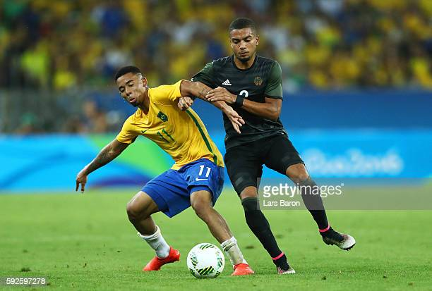 Gabriel Jesus of Brazil holds off Jeremy Toljan of Germany during the Men's Football Final between Brazil and Germany at the Maracana Stadium on Day...