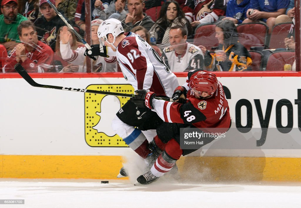 Gabriel Landeskog #92 of the Colorado Avalanche and Jordan Martinook #48 of the Arizona Coyotes collide along the boards as they battle for the puck during the second period at Gila River Arena on March 13, 2017 in Glendale, Arizona.