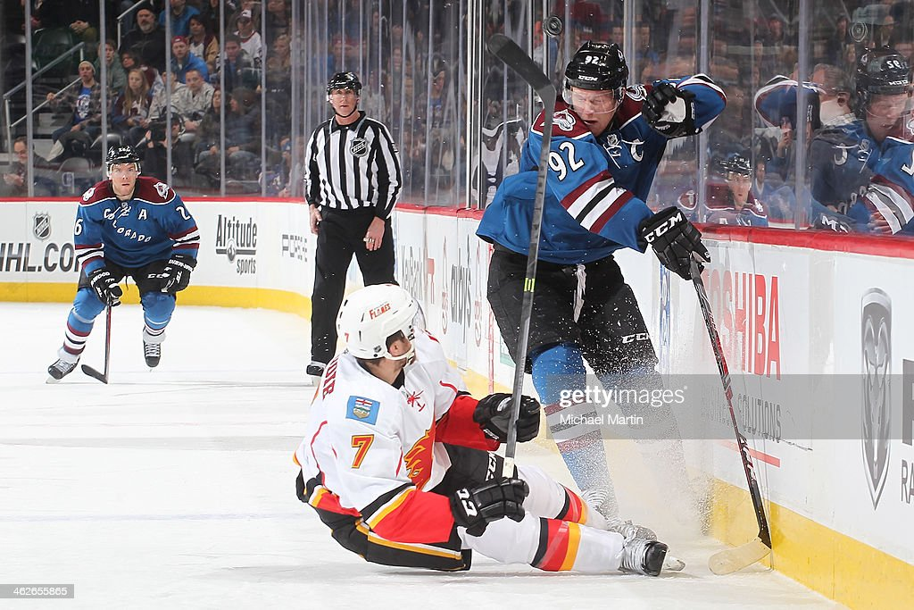 Gabriel Landeskog #92 of the Colorado Avalanche and TJ Brodie #7 the Calgary Flames fight for the puck at the Pepsi Center on January 06, 2014 in Denver, Colorado.