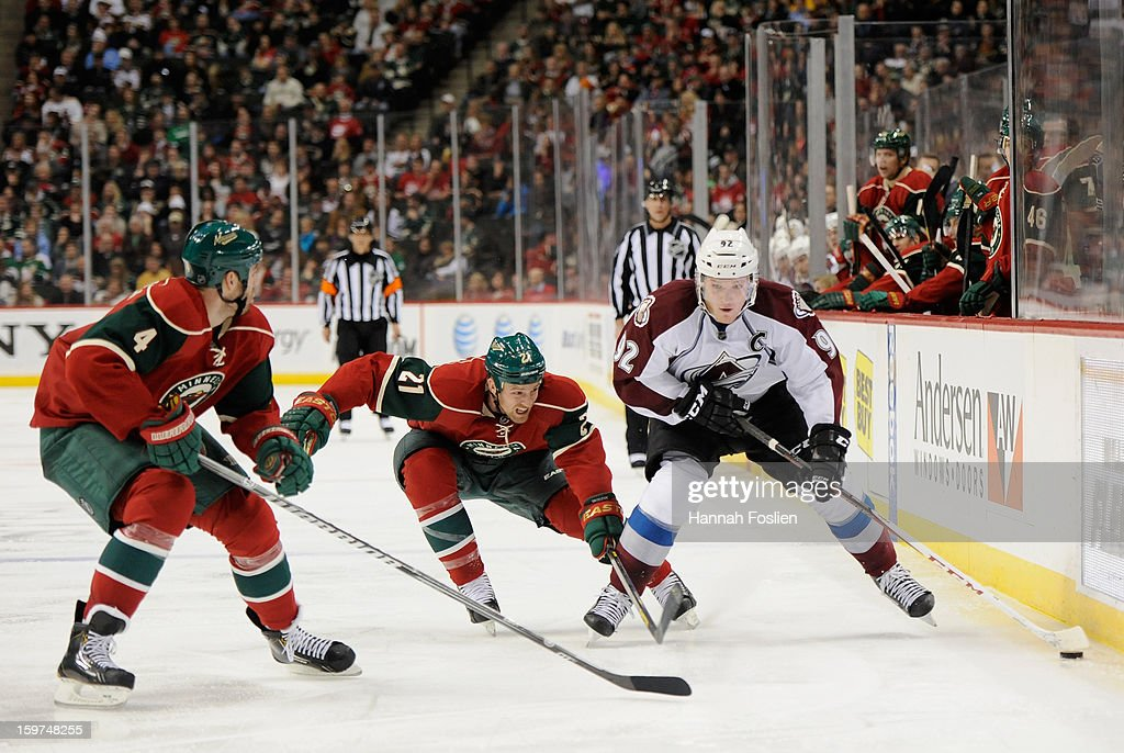 <a gi-track='captionPersonalityLinkClicked' href=/galleries/search?phrase=Gabriel+Landeskog&family=editorial&specificpeople=6590816 ng-click='$event.stopPropagation()'>Gabriel Landeskog</a> #92 of the Colorado Avalanche controls the puck against <a gi-track='captionPersonalityLinkClicked' href=/galleries/search?phrase=Clayton+Stoner&family=editorial&specificpeople=2222214 ng-click='$event.stopPropagation()'>Clayton Stoner</a> #4 and <a gi-track='captionPersonalityLinkClicked' href=/galleries/search?phrase=Kyle+Brodziak&family=editorial&specificpeople=2165412 ng-click='$event.stopPropagation()'>Kyle Brodziak</a> #21 of the Minnesota Wild during the third period of the season opener on January 19, 2013 at Xcel Energy Center in St. Paul, Minnesota. The Wild defeated the Avalanche 4-2.