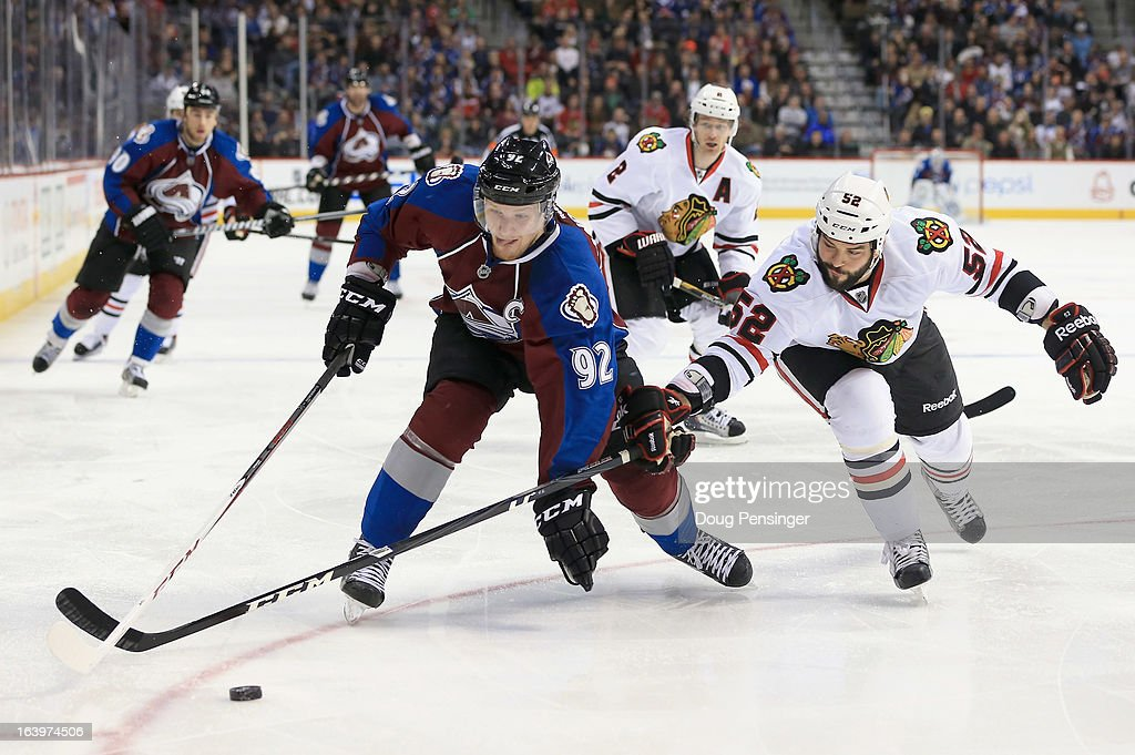 Gabriel Landeskog #92 of the Colorado Avalanche controls the puck against Brandon Bollig #52 of the Chicago Blackhawks at the Pepsi Center on March 18, 2013 in Denver, Colorado.