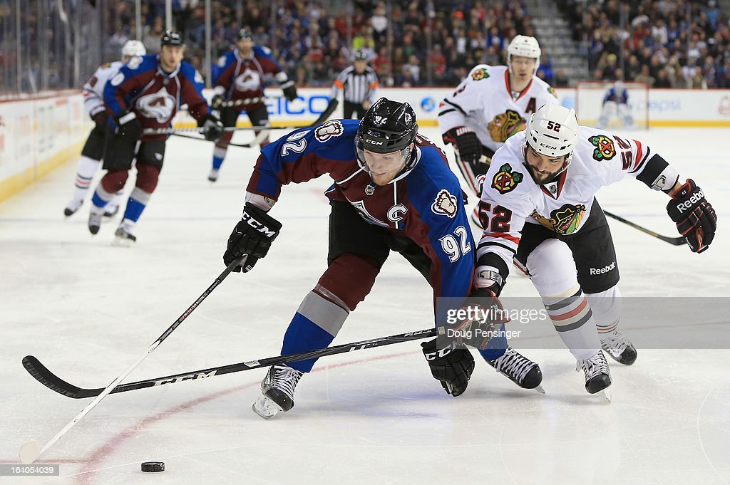 Gabriel Landeskog #92 of the Colorado Avalanche controls the puck against Brandon Bollig #52 of the Chicago Blackhawks at the Pepsi Center on March 18, 2013 in Denver, Colorado. The Blackhawks defeated the Avalanche 5-2.