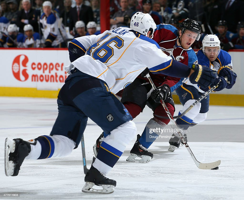 Gabriel Landeskog of the Colorado Avalanche controls the puck against Roman Polak and Kevin Shattenkirk of the St Louis Blues at Pepsi Center on...