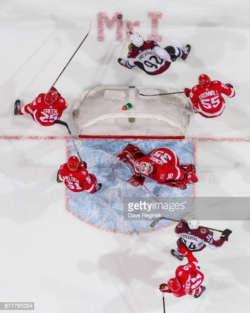 Gabriel Landeskog of the Colorado Avalanche controls the puck behind the net between Mike Green and Niklas Kronwall of the Detroit Red Wings during...