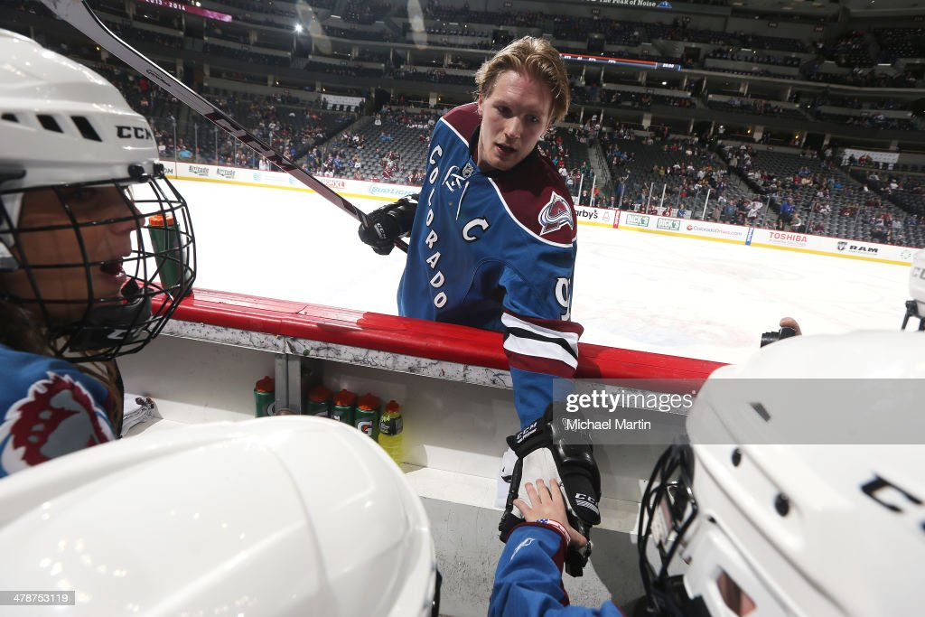 Gabriel Landeskog #92 of the Colorado Avalanche hands a puck to a young fan prior to the game against the Anaheim Ducks at the Pepsi Center on March 14, 2014 in Denver, Colorado.