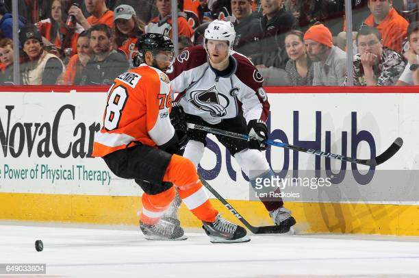 Gabriel Landeskog of the Colorado Avalanche keeps his eye on the loose puck against PierreEdouard Bellemare of the Philadelphia Flyers on February 28...