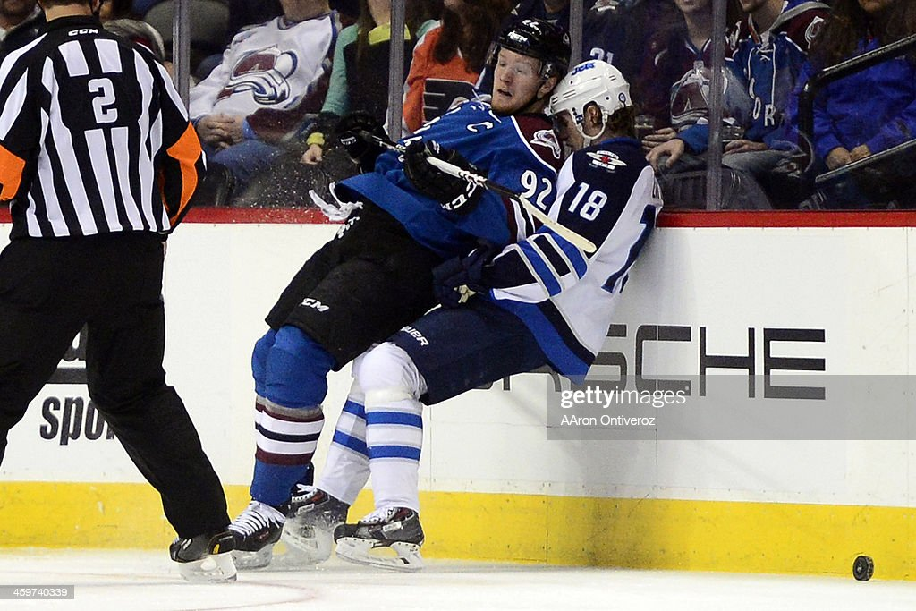 Gabriel Landeskog (92) of the Colorado Avalanche, leans back on Bryan Little (18) of the Winnipeg Jets after checking him during the first period of action. The Colorado Avalanche hosted the Winnipeg Jets at the Pepsi Center on Sunday, December 29, 2013.