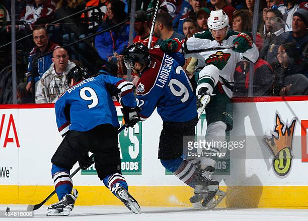 Gabriel Landeskog of the Colorado Avalanche puts a hit on Jason Pominville of the Minnesota Wild as Matt Duchene of the Colorado Avalanche controls...