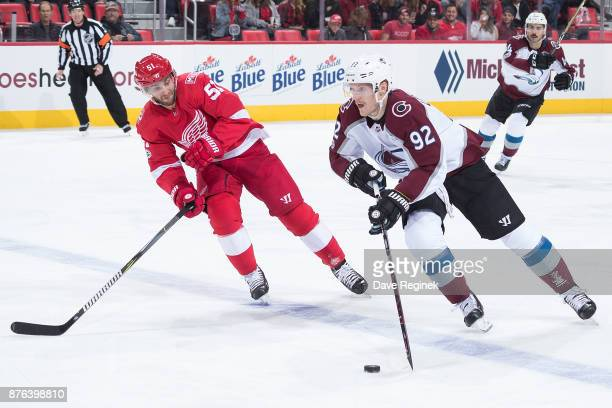 Gabriel Landeskog of the Colorado Avalanche skates up ice with the puck followed by Frans Nielsen of the Detroit Red Wings during an NHL game at...