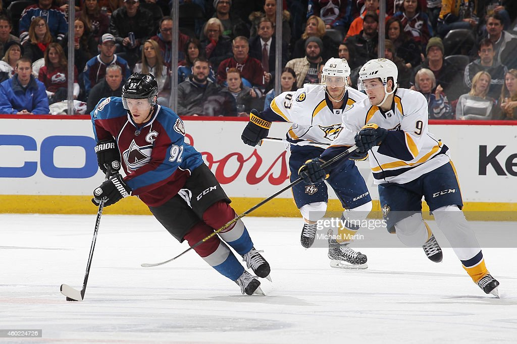Gabriel Landeskog #92 of the Colorado Avalanche skates with the puck pursued by Filip Forsberg #9 and Mike Ribeiro #63 of the Nashville Predators at the Pepsi Center on December 9, 2014 in Denver, Colorado. The Predators defeated the Avalanche 3-0.