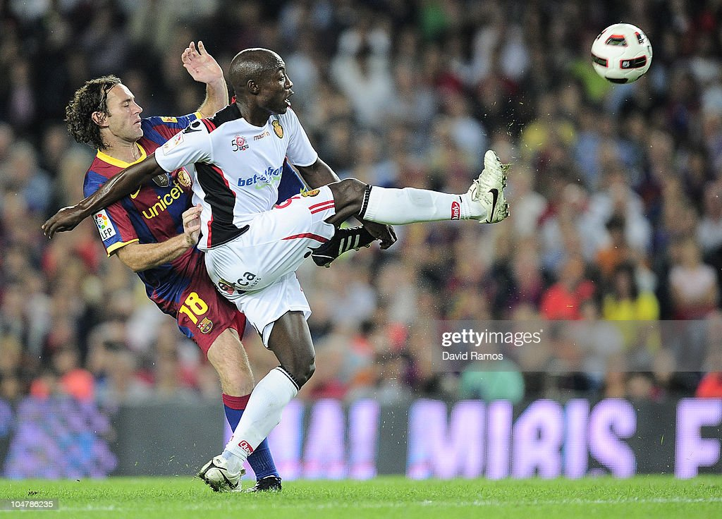 <a gi-track='captionPersonalityLinkClicked' href=/galleries/search?phrase=Gabriel+Milito&family=editorial&specificpeople=490871 ng-click='$event.stopPropagation()'>Gabriel Milito</a> of Barcelona (L) duels for a high ball with <a gi-track='captionPersonalityLinkClicked' href=/galleries/search?phrase=Pierre+Webo&family=editorial&specificpeople=790636 ng-click='$event.stopPropagation()'>Pierre Webo</a> of Mallorca reacts during the La Liga match between Barcelona and Mallorca at the Camp Nou stadium on October 3, 2010 in Barcelona, Spain. The match ended 1-1 draw.