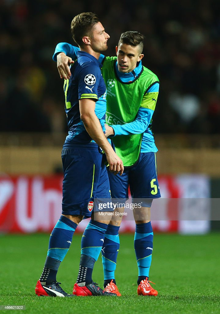 Gabriel of Arsenal (5) consoles team mate Olivier Giroud as they are eliminated after the UEFA Champions League round of 16 second leg match between AS Monaco and Arsenal at Stade Louis II on March 17, 2015 in Monaco, Monaco. Arsenal won the match 2-0, but lost on the away goals rule.