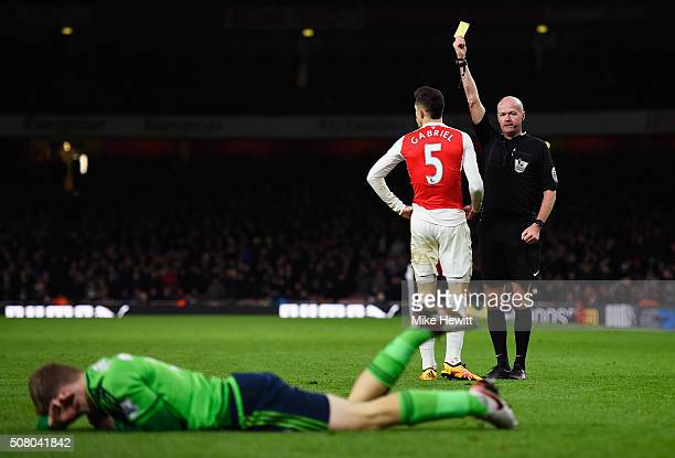 Gabriel of Arsenal is shown a yellow card by referee Lee Mason during the Barclays Premier League match between Arsenal and Southampton at the...
