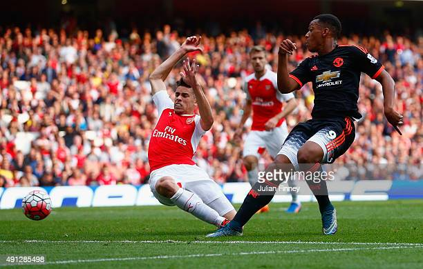 Gabriel Paulista of Arsenal attempts to block Anthony Martial of Manchester United during the Barclays Premier League match between Arsenal and...