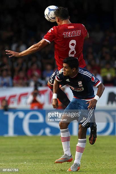 Gabriel Pe–nalba of Veracruz heads the ball over the mark of Jesus Sanchez of Chivas during a 1st round match between Veracruz and Chivas as part of...