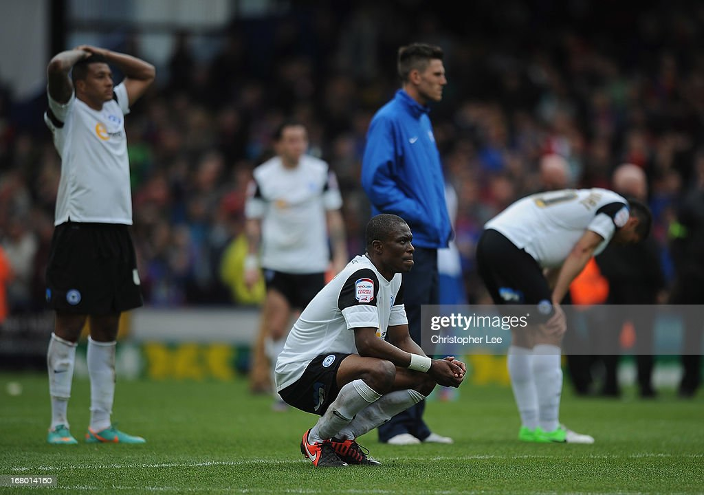 Gabriel Zakuani of Peterborough looks dejected with his team mates after they are relegated during the npower Championship match between Crystal Palace and Peterborough United at Selhurst Park on May 04, 2013 in London, England.