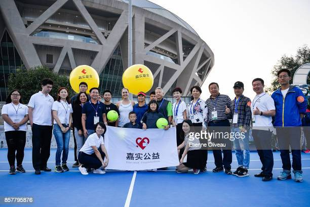 Gabriela Dabrowski of Canada and Yifan Xu of China poses with kids and staff members during the Inclub Clinic on day six of the 2017 China Open at...