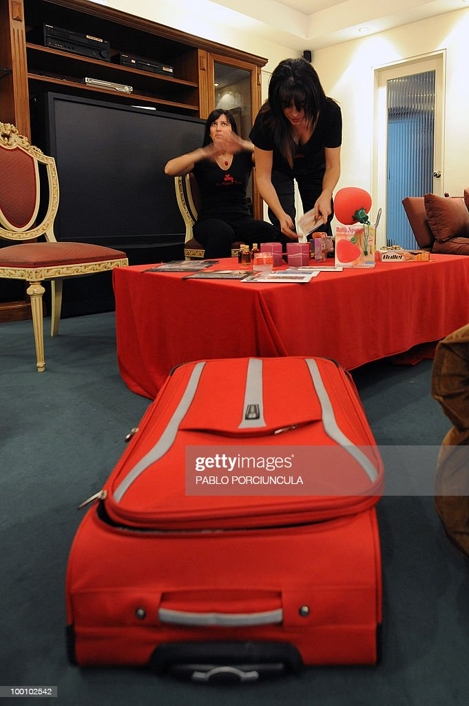 Gabriela Perez (R) and Nicole Komin, representatives for Latin America of 'La Maleta Roja' (The Red Suitcase) company, promote sex toys in Montevideo, Uruguay, on May 15, 2010. The Spanish company, specializing in erotic toys, lingerie and cosmetics, sells its products through saleswomen who go to friends meetings at homes. AFP PHOTO/Pablo PORCIUNCULA