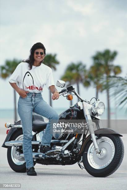 Gabriela Sabatini of Argentina poses for a portrait standing beside a HarleyDavidson Fatboy FLSTF motorcycle during the ATP Lipton Tennis...