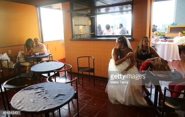 Gabrieli sits at an afterparty after marrying lover Joyce at what was billed as the world's largest communal gay wedding on December 8 2013 in Rio de...