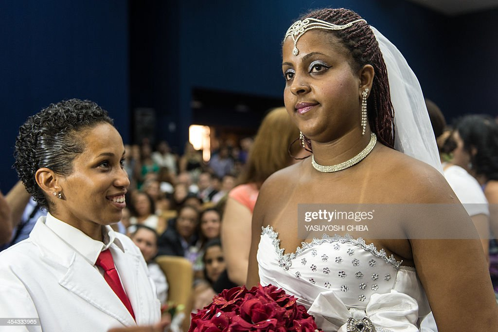 Gabrielle Costa (R) and Joyce Xavier gesture during their wedding ceremony at the Court of Justice of the State of Rio de Janeiro in Rio de Janeiro, Brazil, on December 8, 2013. 130 gay couples are getting married in the first massive wedding ceremony since the first gay marriage in Rio de Janeiro in 2011.