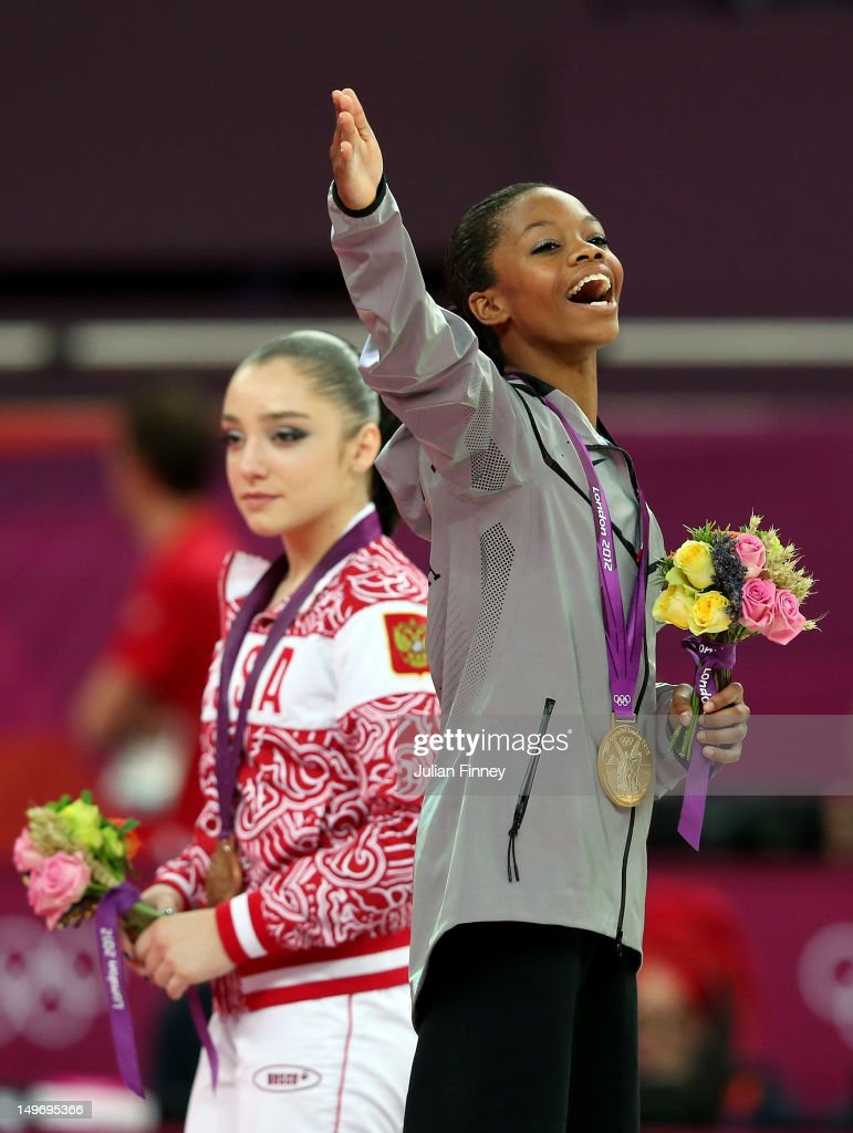 Gabrielle Douglas of the United States celebrates on the podium after winning the gold medal in the Artistic Gymnastics Women's Individual AllAround...