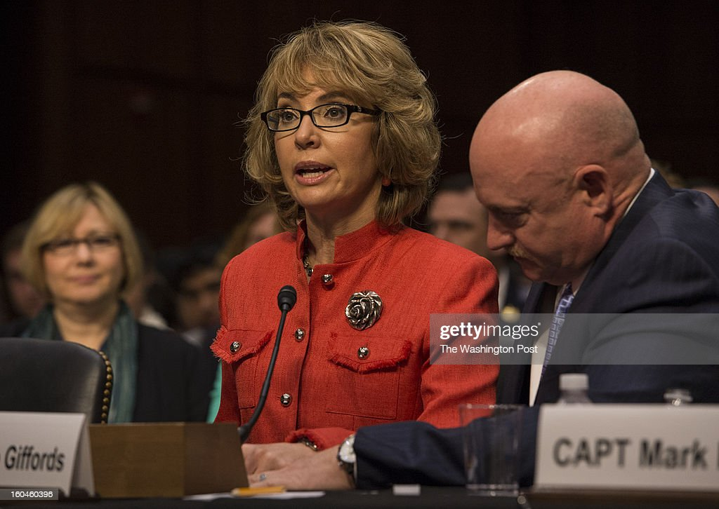 """JANUARY 29 -- Gabrielle Giffords with her husband Captain Mark Kelly at her side gives a brief statement before the Senate Judiciary Committee on gun control in Washington, D.C., on Wednesday, January 29, 2013. """"You must act. Be bold. Be courageous. Americans are counting on you.' told the Committee."""