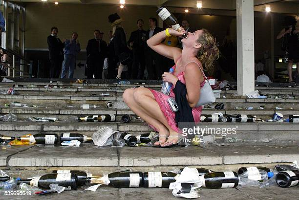 Gabrielle Lucchesi from WA enjoys some champagne on the steps of the stands at the end of the Melbourne Cup at Flemington Racecourse 2 November 2004...