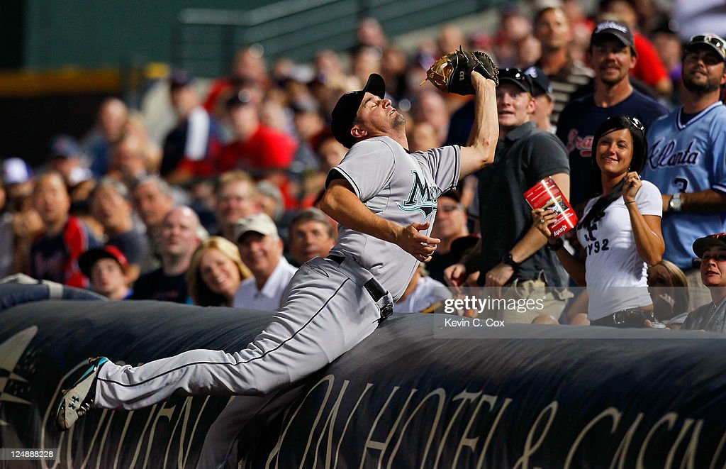 Gaby Sanchez of the Florida Marlins dives into the stands to catch a foul ball by Alex Gonzalez of the Atlanta Braves in the fourth inning at Turner...