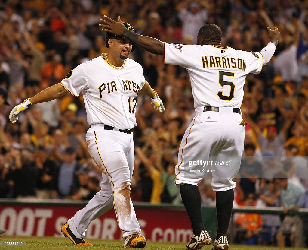 Gaby Sanchez of the Pittsburgh Pirates celebrates with Josh Harrison after hitting a game winning sacrifice fly to center in the ninth inning against...