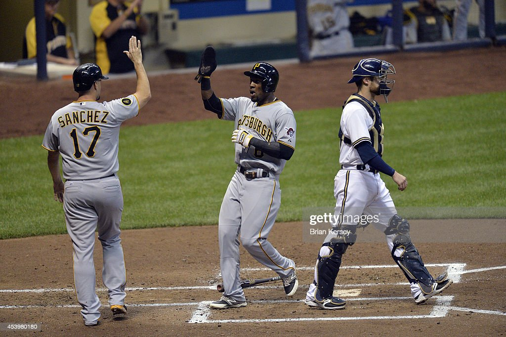 Gaby Sanchez #17 of the Pittsburgh Pirates high-fives teammate Starling Marte #6 after they scored on an RBI double hit by teammate Josh Harrison as catcher Jonathan Lucroy #20 of the Milwaukee Brewers stands on the field during the second inning at Miller Park on August 22, 2014 in Milwaukee, Wisconsin.