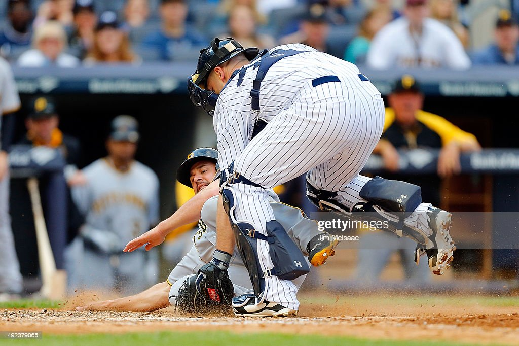 Gaby Sanchez of the Pittsburgh Pirates is tagged out by Brian McCann of the New York Yankees at Yankee Stadium on May 17 2014 in the Bronx borough of...