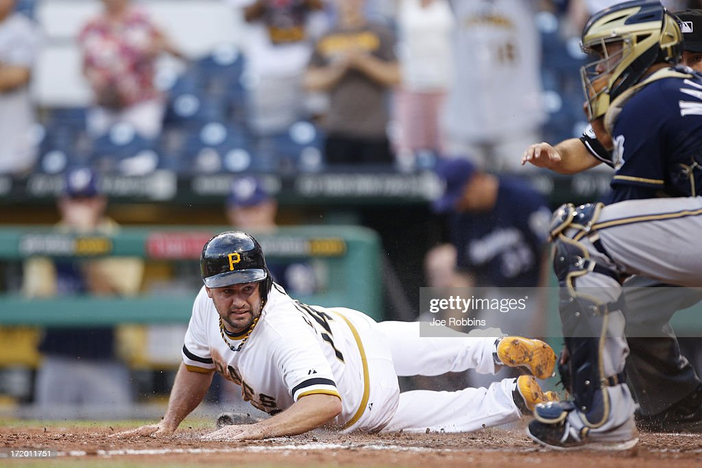 Gaby Sanchez of the Pittsburgh Pirates slides home with the winning run after a single by Russell Martin in the 14th inning of the game against the...