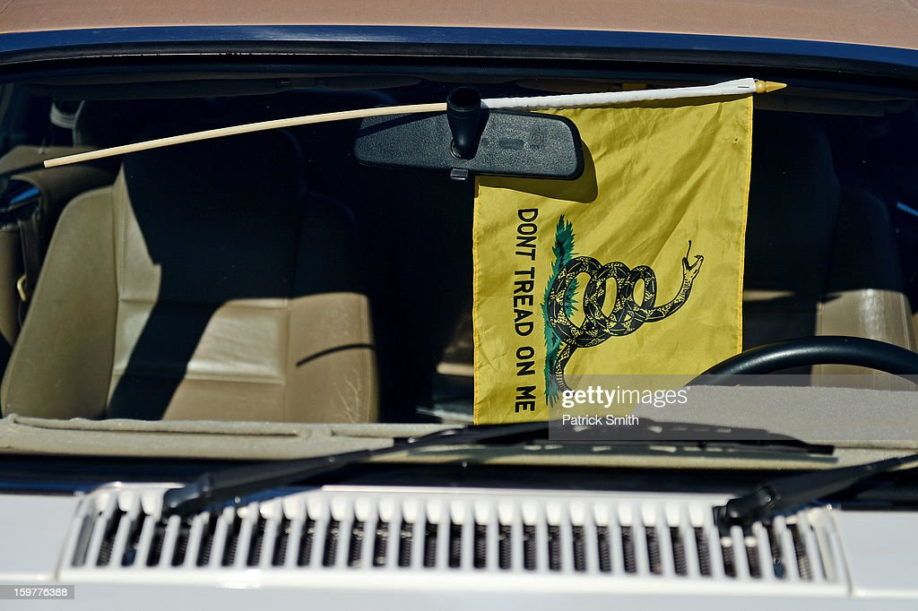 A Gadsden flag hangs from a rearview mirror of a car in the parking lot during the Delaware State Sportsmen's Association Second Amendment rally at the Modern Maturity Center on January 20, 2013 in Dover, Delaware. U.S. President Barack Obama recently unveiled a package of gun control proposals that include universal background checks and bans on assault weapons and high-capacity magazines.