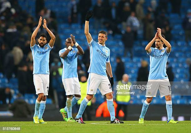 Gael Clichy Martin Demichelis and Jesus Navas of Manchester City salute the crowd as they reach the quarter finals after the UEFA Champions League...