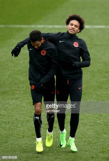 Gael Clichy of Manchester City and Leroy Sane of Manchester City share a smile during a Manchester City training session prior to the UEFA Champions...