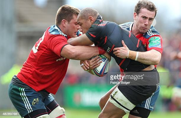 Gael Fickou of Toulouse is tackled by CJ Stander and JJ Hanrahan of Munster during the Heineken Cup Quarter Final match between Munster and Toulouse...