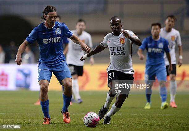 Gael Kakuta of Hebei CFFC competes for the ball with Anders Svensson of Guangzhou RF during their Chinese Super League football match in Guangzhou on...