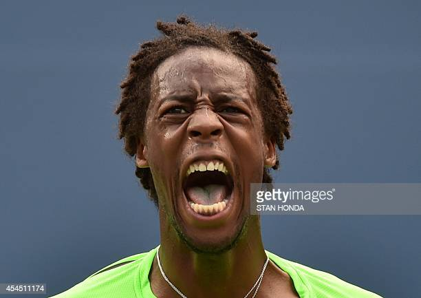 Gael Monfils of France celebrates after winning the second set in a tiebreaker over Grigor Dimitrov of Bulgaria during their 2014 US Open men's...